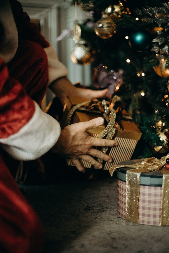 santa leaving gifts under the  christmas tree
