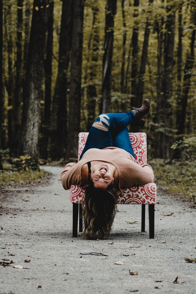 laughing girl upside down in chair