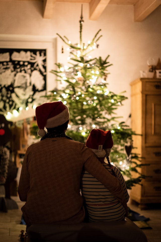 siblings sitting in front of the christmas tree
