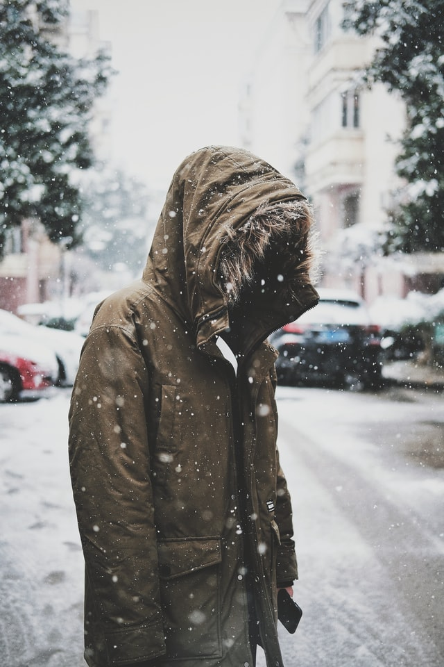 standing in the snowfall on a busy street