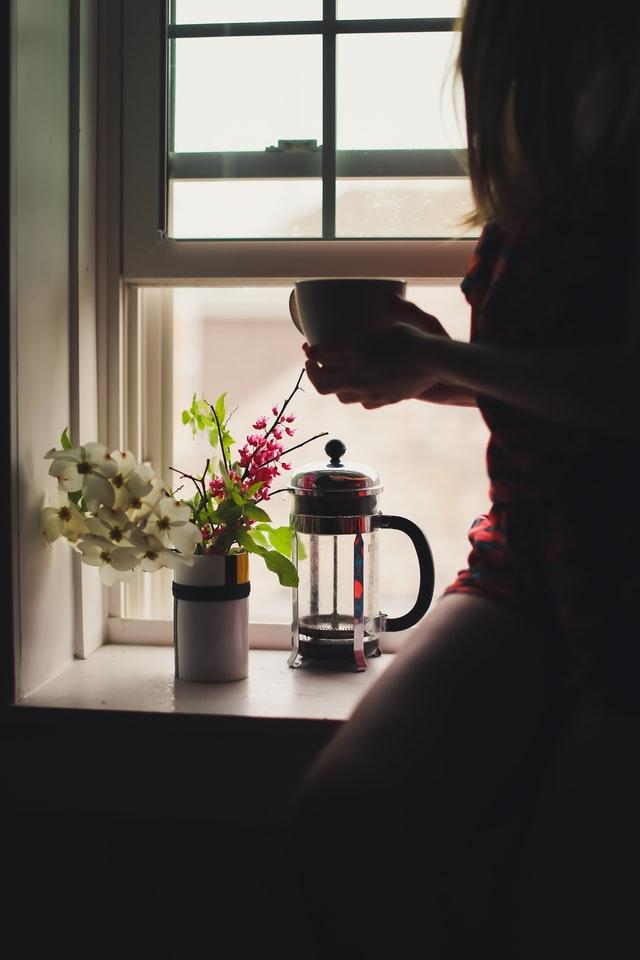 woman sitting in windowsill drinking coffee looking out window
