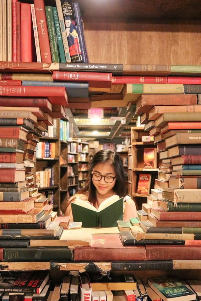 Girl reading amongst stack of books